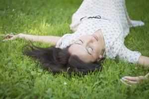 Frau liegt auf Rasen