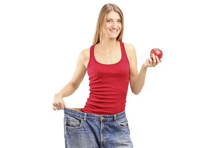 Frau die in ihrer alten Hose steht mit einem Apfel in der Hand