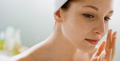Eine junge Frau cremt sich das Gesicht ein.