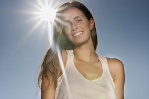 Junge Frau mit Sonne im Hintergrund
